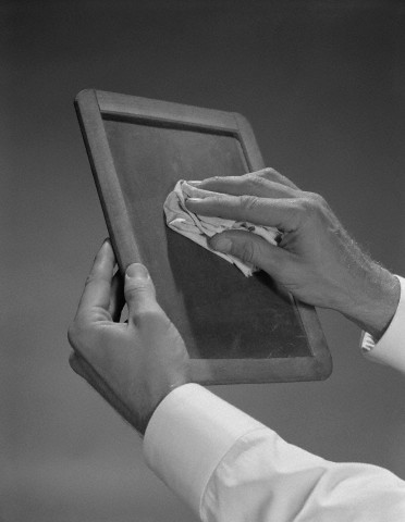 Male hands wiping slate clean